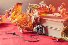 Lebens- alte Bücher des Weinleseherbstes noch mit Uhren nähern sich trockenen Ahornblättern Lizenzfreies Stockbild