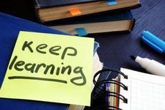Lebenslanges Lernen Buch und Blatt Papier mit Wörtern halten zu lernen lizenzfreie stockfotografie