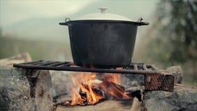 Lebensmittel über einem Lagerfeuer im Wald stock footage