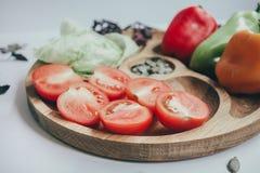 Lebensmittel-, Ernährungs- und Nahrungskonzept - geschnittener Kürbis und anderes Gemüse auf hölzernem Brett Frischgemüse und Grü lizenzfreie stockfotos