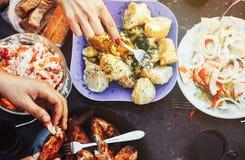 Lebensmittel-Konzept-Freunde an einem Abendtische mit unterschiedlichem Lebensmittel stockbilder