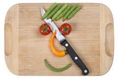 Lebensmittel mit lächelndem Gemüsegesicht des Messers an zubereiten und kochend Lizenzfreie Stockfotos