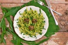Lebensmittel mit Teigwaren, grünem Pesto, Fleischklöschen und Buckram auf weißer Platte auf hölzernem Hintergrund lizenzfreie stockbilder