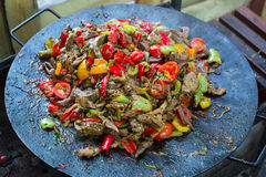 Lebensmittel-Rindfleisch bbq auf Grill mit Feuer diente mit Tomaten und Bratengemüse Lizenzfreie Stockbilder
