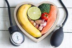 Lebensmittel und gesundes Herzdiätkonzept mit Blut preasure Messgerät auf weißen Planken lizenzfreies stockbild