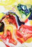 Lebensmittelfarbe auf Milchzusammenfassungshintergrund, Marmor mögen Stockbild