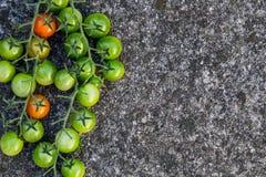 Lebensmittelhintergrund: grüne, rote Kirschtomaten, Steinhintergrund, Draufsicht Stockbilder