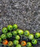 Lebensmittelhintergrund: grüne, rote Kirschtomaten, Steinhintergrund, Draufsicht Stockfotografie