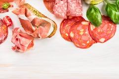 Lebensmittelhintergrund mit unterschiedlichem italienischem Wurst-, Schinken-, Brot- und Basilikum Pestosandwich Lizenzfreies Stockbild
