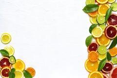 Lebensmittelhintergrund withs Scheiben der Vielzahlzitrusfrucht Draufsicht mit Co Stockfotografie