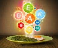 Lebensmittelplatte mit köstlicher Mahlzeit und gesunden Vitaminsymbolen Lizenzfreies Stockbild