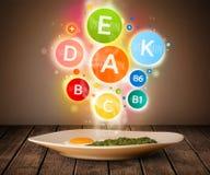 Lebensmittelplatte mit köstlicher Mahlzeit und gesunden Vitaminsymbolen Stockbilder