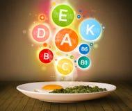 Lebensmittelplatte mit köstlicher Mahlzeit und gesunden Vitaminsymbolen Stockfoto