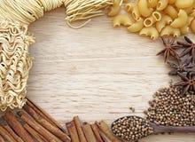 Lebensmittelrahmen, Nudel, Pfefferkorn, Makkaronidesign auf hölzernem Hintergrund Stockfotografie