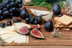 Lebensmittelstillleben mit Käse, Trauben und Feigen Stockfotos