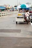 Lebensmittelverkäufermädchen auf einem motorisierten Warenkorb, der abgezogene Ananas verkauft Stockfoto