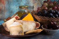 Lebensmittelzusammensetzung mit Blöcken des schimmeligen Käses, in Essig eingelegte Pflaumen, gra Lizenzfreie Stockbilder