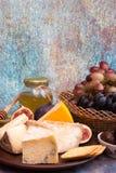 Lebensmittelzusammensetzung mit Blöcken des schimmeligen Käses, in Essig eingelegte Pflaumen, gra Stockfotografie