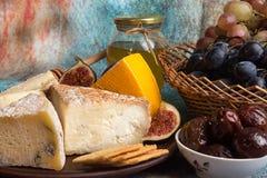 Lebensmittelzusammensetzung mit Blöcken des schimmeligen Käses, in Essig eingelegte Pflaumen, gra Lizenzfreies Stockbild