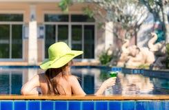 Lebensstil-asiatische Frau im Badeanzug entspannend und glücklich mit Cocktail auf Liege nahe Swimmingpool, Sommertag Stockbild