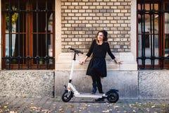 Lebensstil in der modernen Stadt mit attraktiver Frau auf elektrischem Roller Stockbilder
