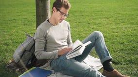 Lebensstil des Unternehmer-Geschäftsmannes der Person des jungen vorbildlichen traurigen Sitzens auf Gras- und Lesedokument und d stock video footage