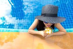 Lebensstil-Frau im Badeanzug entspannend und glücklich mit Cocktail auf Liege nahe Swimmingpool, Sommertag Lizenzfreie Stockbilder