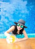 Lebensstil-Frau im Badeanzug entspannend und glücklich mit Cocktail auf Liege nahe Swimmingpool, Sommertag, ausgewählter Fokus Stockfotos