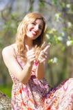 Lebensstil-Ideen Glückliche und lächelnde kaukasische blonde Frau im blumigen Kleid Stockfoto