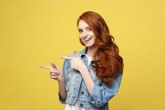 Lebensstil-Konzept: Glückliches aufgeregtes cuacaisan touristisches Mädchen, das Finger auf dem Kopienraum lokalisiert auf golden lizenzfreies stockfoto