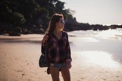 Lebensstil-Modeporträt des Sommers sonniges der jungen stilvollen Hippie-Frau, die auf Strand, tragende nette modische Ausstattun Stockbilder