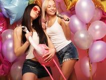 Lebensstil-, Partei- und Leutekonzept: Glückliche Mädchen mit microphon Lizenzfreie Stockfotos