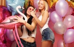 Lebensstil-, Partei- und Leutekonzept: Glückliche Mädchen mit microphon Stockfotografie