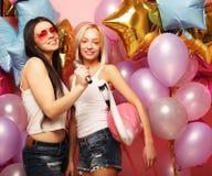 Lebensstil-, Partei- und Leutekonzept: Glückliche Mädchen mit microphon Stockfoto
