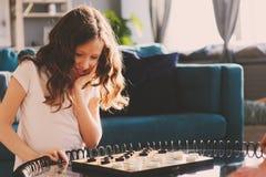 Lebensstil schoss vom intelligenten Kindermädchen, das zu Hause Kontrolleure spielt Stockfoto
