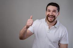 Lebensstil und Leutekonzept: Tragendes weißes T-Shirt des glücklichen gutaussehenden Mannes, das Daumen oben über lokalisiertem H lizenzfreie stockfotografie