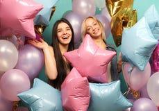 Lebensstil und Leutekonzept: zwei Freundinnen mit den colorfoul Luftballonen - jung und glücklich Stockbild