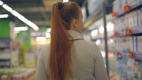 Lebensstilfrau geht zum Lebensmittelgeschäftsupermarkt mit einem Wagen stock footage