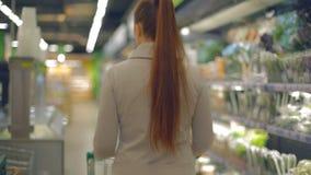 Lebensstilfrau geht zum Lebensmittelgeschäftsupermarkt mit einem Wagen stock video footage