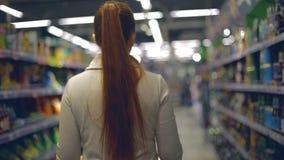 Lebensstilfrau geht zum Lebensmittelgeschäftsupermarkt mit einem Wagen stock video