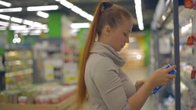 Lebensstilfrau wählt Milchprodukte im Supermarkt stock video footage
