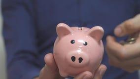 Lebensstilgeschäftsmann macht Spareinlagen einsetzt Münzen in ein Sparschwein Sparschweingeschäftskonzept Zeitlupevideo einsparun stock footage