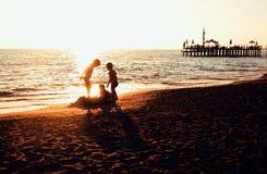 Lebensstilleutekonzept: Schattenbild mit drei kleinen Jungen auf dem Sonnenuntergangstrand, der im Wasser spielt Lizenzfreie Stockfotografie