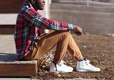 Lebensstilmodefoto, das stilvoller afrikanischer Mann Musik hört, genießt den Sonnenuntergang und trägt das rote Hemd des Hippie- Stockfotografie