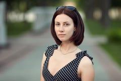 Lebensstilporträt bilden erwachsene entzückende frische schauende Brunettefrau ohne die Pendelfrisur, die den Abendpark aufwirft, Stockfoto