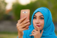 Lebensstilporträt der jungen glücklichen und schönen touristischen Frau in moslemischem hijab Kopftuch, das selfie Foto mit Handy lizenzfreies stockfoto