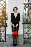 Lebensstilporträt der jungen stilvollen Frau geht in die Stadt mit einer roten modischen Tasche Auf der Mädchenschulter-Handtasch Stockbild
