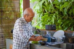 Lebensstilporträt des älteren glücklichen und süßen asiatischen japanischen Mannes im Ruhestand, der zu Hause die Küche allein or lizenzfreie stockbilder