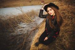 Lebensstilportr?t der jungen Frau im schwarzen Hut, der durch den See an einem sch?nen und warmen Herbsttag stillsteht stockfotografie