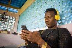 Lebensstilportr?t des jungen afroen-amerikanisch Mannes des attraktiven und k?hlen Hippie-Schwarzen unter Verwendung der Handy- u stockfoto